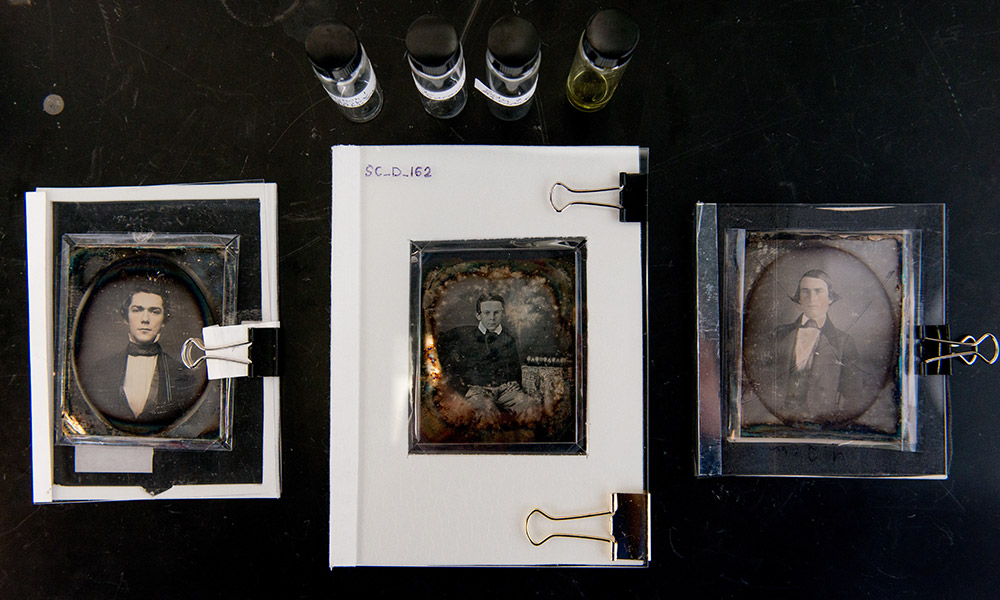 daguerreotypes on a table along with some chemicals in jars