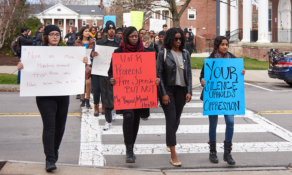 student protester march with signs that read YOUR SILENCE UPHOLDS OPRESSION
