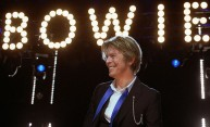 David Bowie under a glowing sign that reads BOWIE