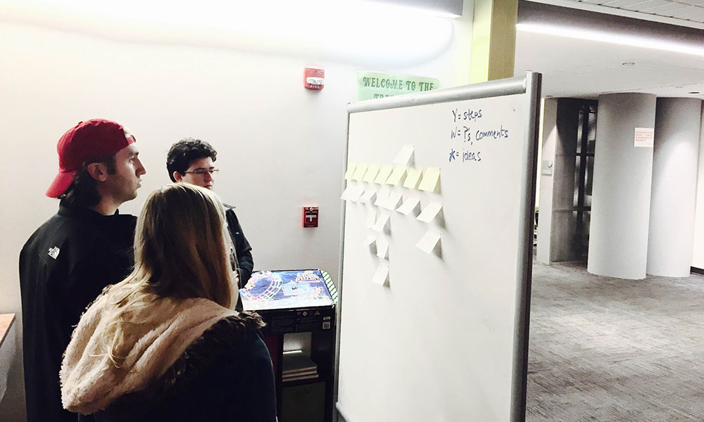 three students standing in front of a white board