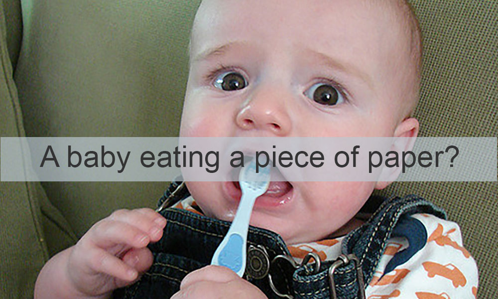 image of a baby with a tootbrush features the words A BABY EATING A PIECE OF PAPER?
