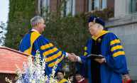 Joseph Cunningham and Joel Seligman shaking hands at commencement
