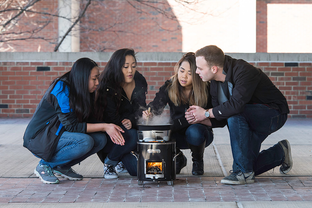students sitting around a cooking stove
