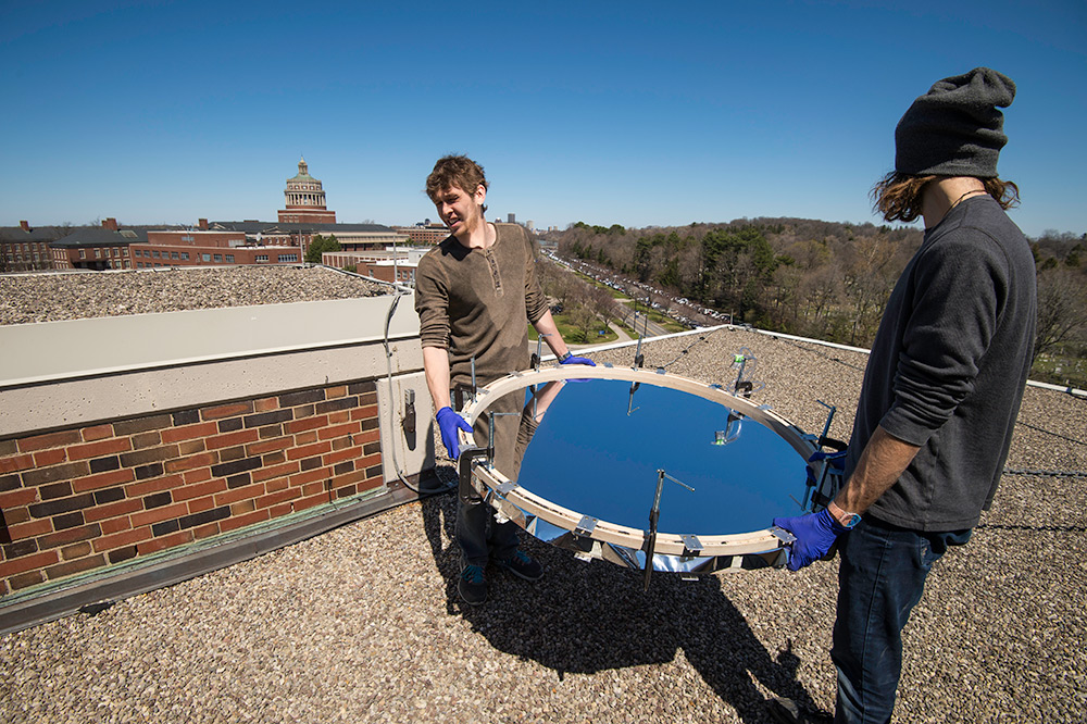 student carry round solar mirror onto roof, library tower in the background