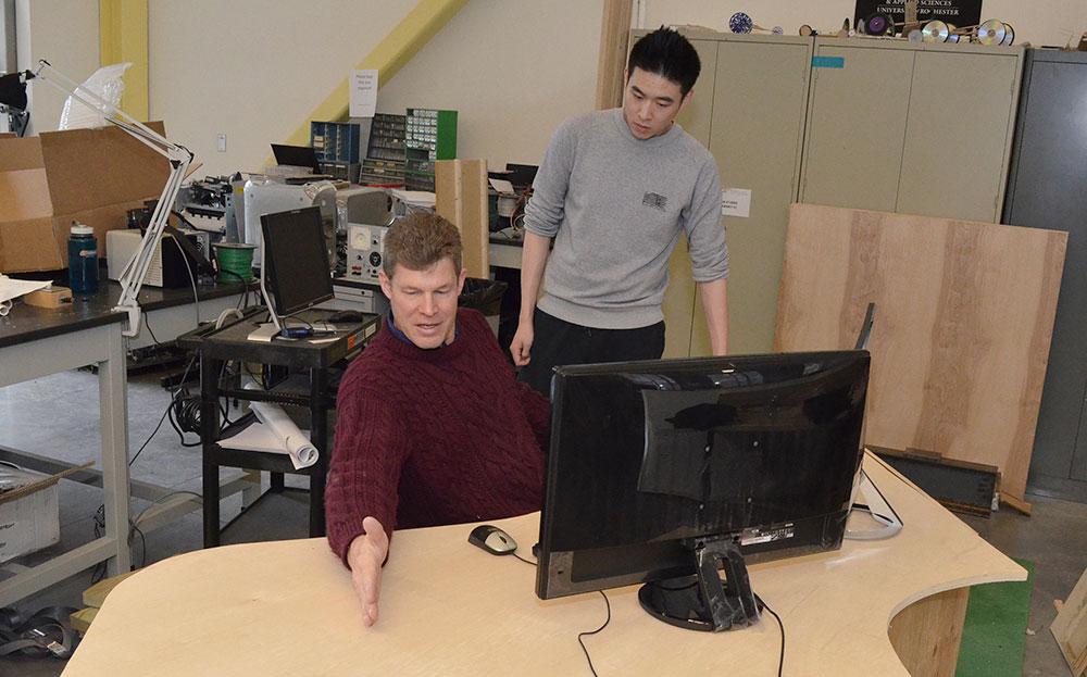 student and professor examine a prototype desk