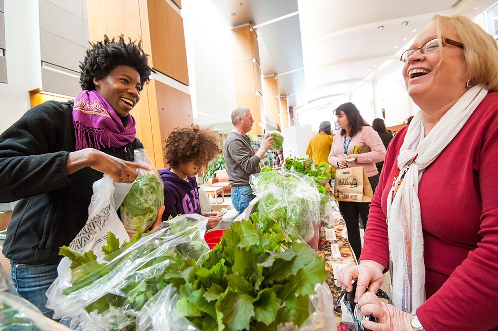 farmers market customer receives vegetables from vendor