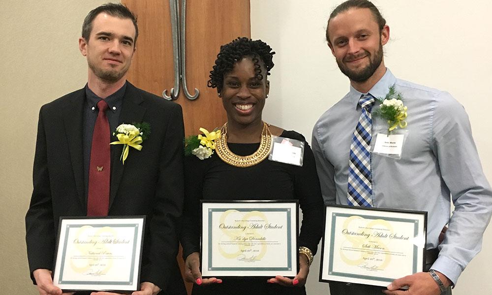 portrait of three students holding awards.