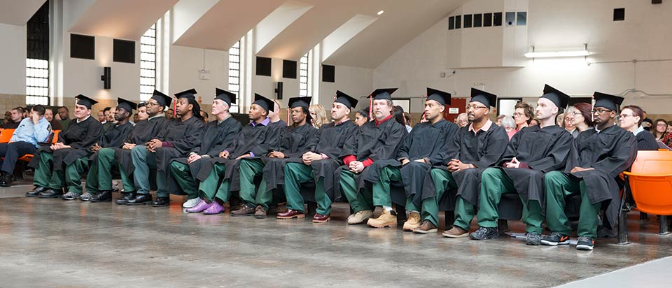 group of graduates sit in a row