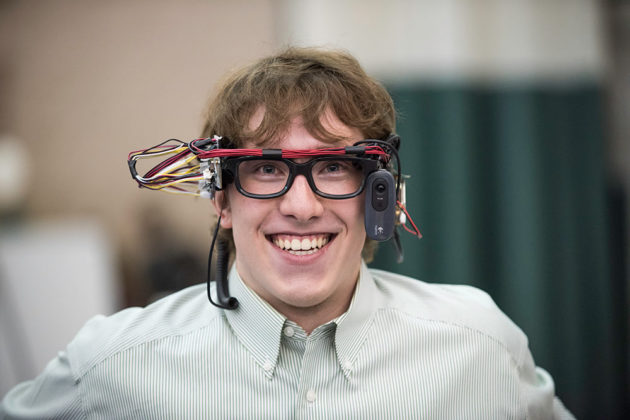student smiles while wearing glasses connected to a computer