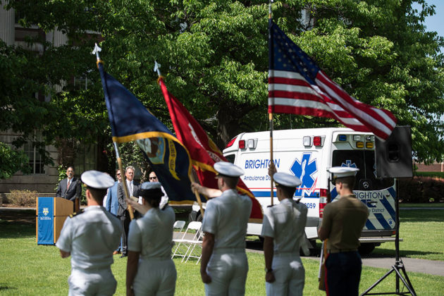 color guard stands in front of an ambulance parked on the Eastman quad