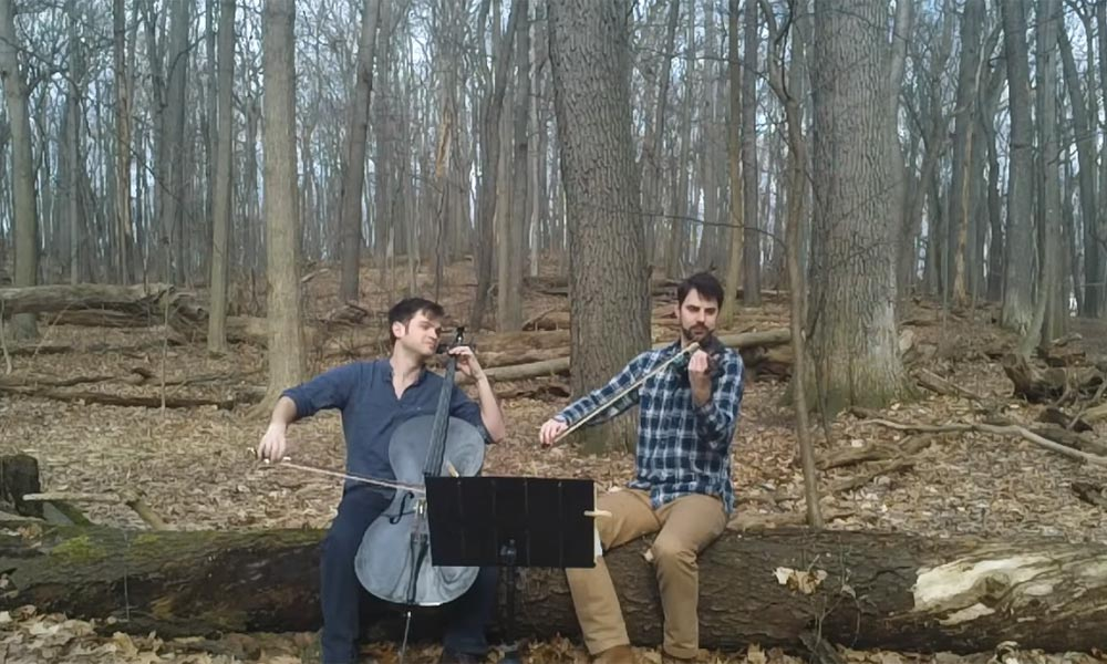 cellist and violinist perform outdoors
