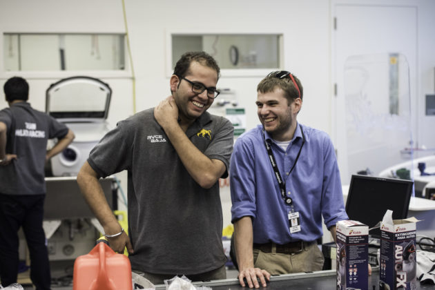 Yash Mehrotra from India's Team Helios, left, shares a laugh with Kevin Bonko '17, president of Rochester's Baja team, at the fabrication lab in Rettner Hall.