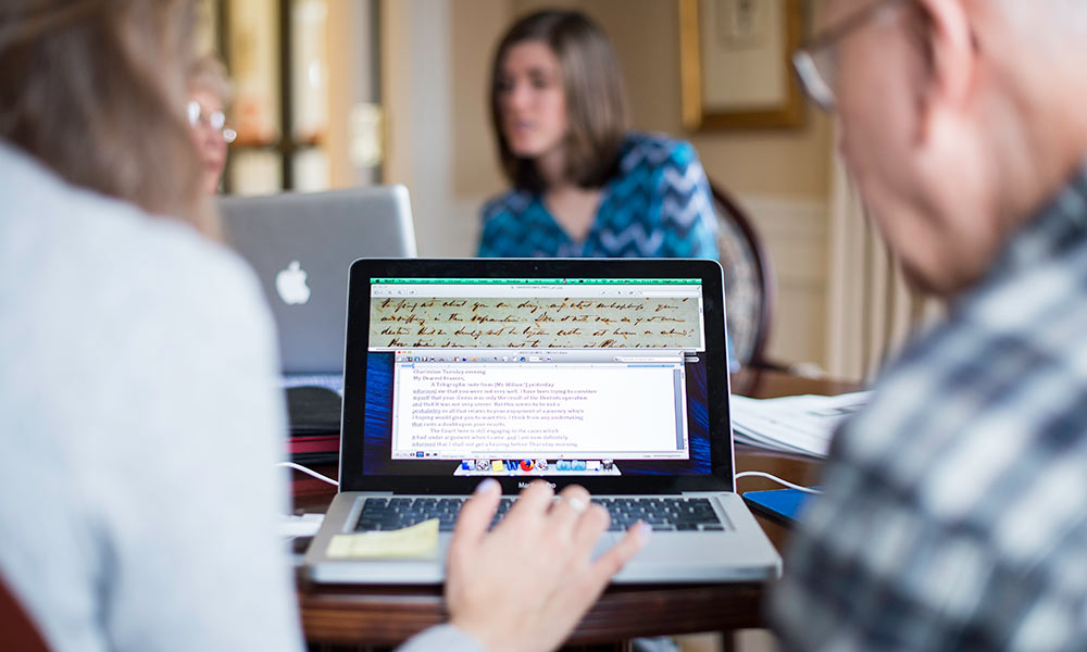 photo of students and older volunteers at a laptop