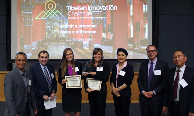 Six students stand with Duncan Moore before a screen showing the Tibetan Innovation Challenge logo