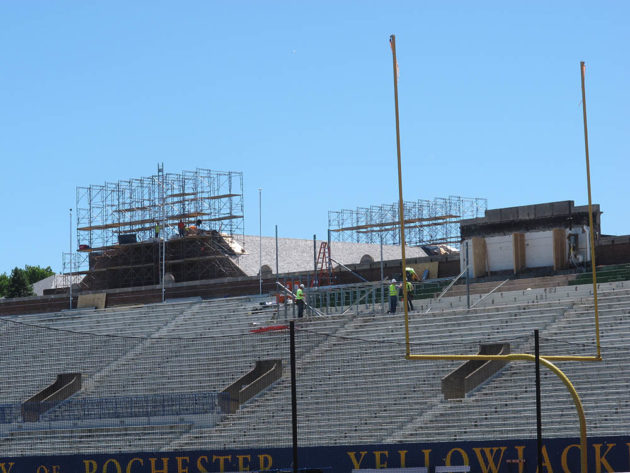 construction workers on top of Fauver Stadium bleachers.