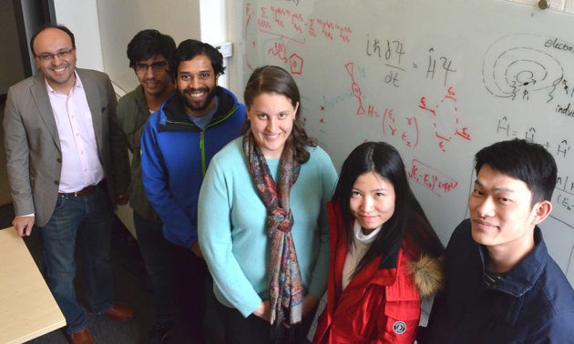 professor poses with students in front of white board