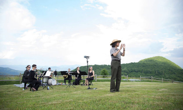 musicians performing outdoors on a hillside, being introduced by a park service ranger