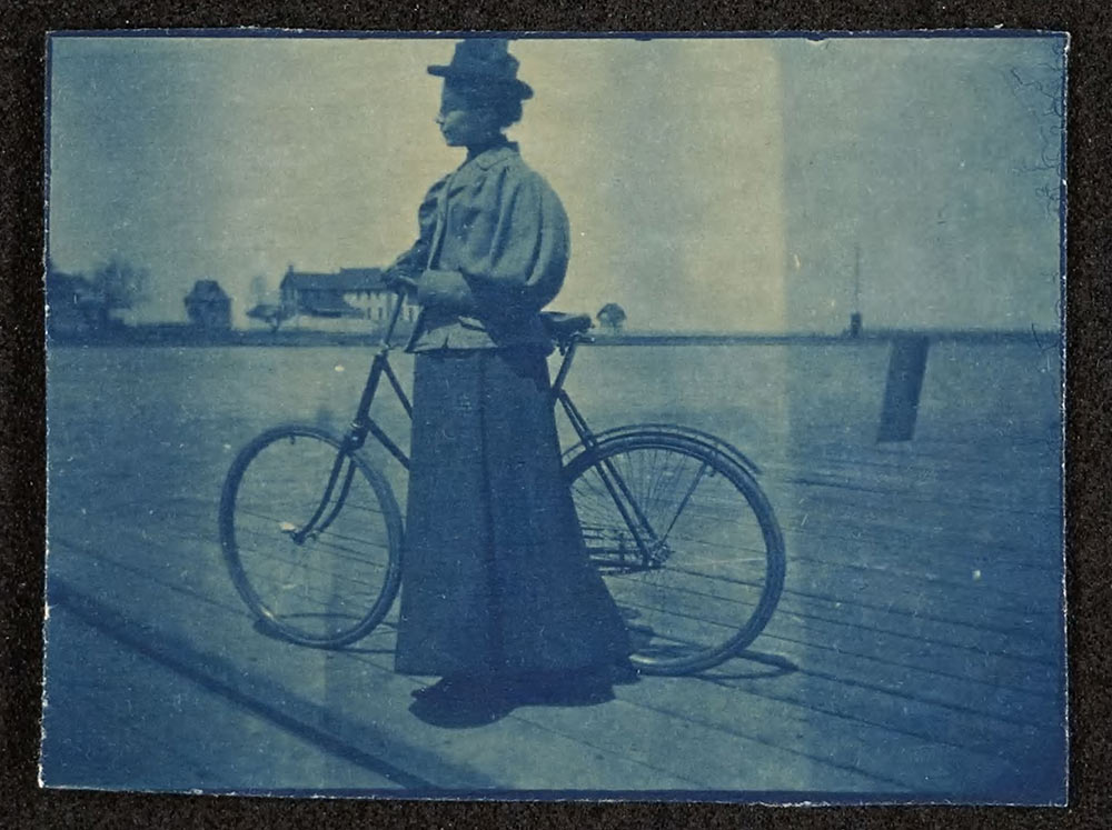 Woman in a long dress standing by a bicycle in the year 1897