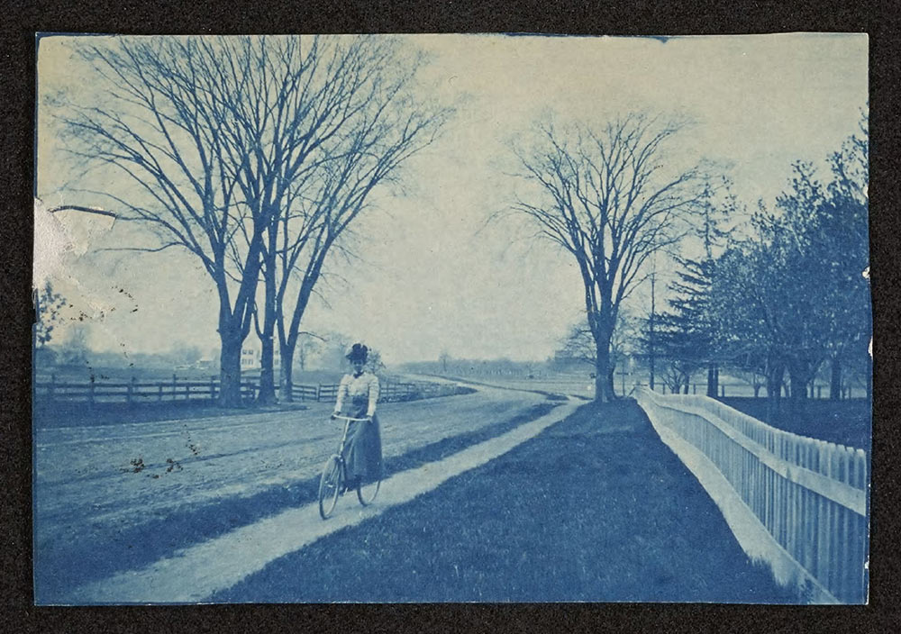 old bluish photo of woman riding a bicycle along a path in the year 1900