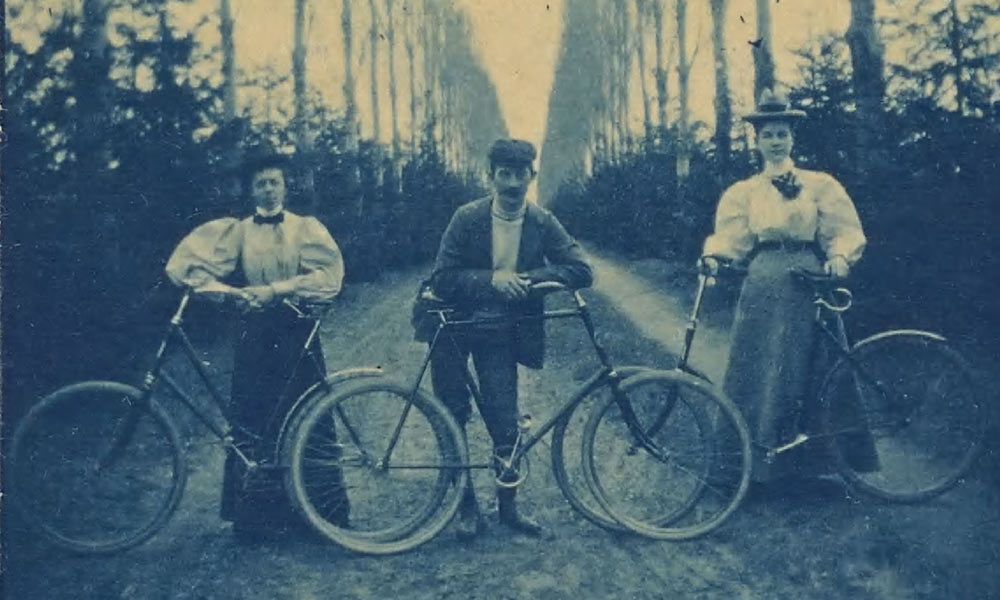 Two women and a man stand with their bicycles in the year 1897
