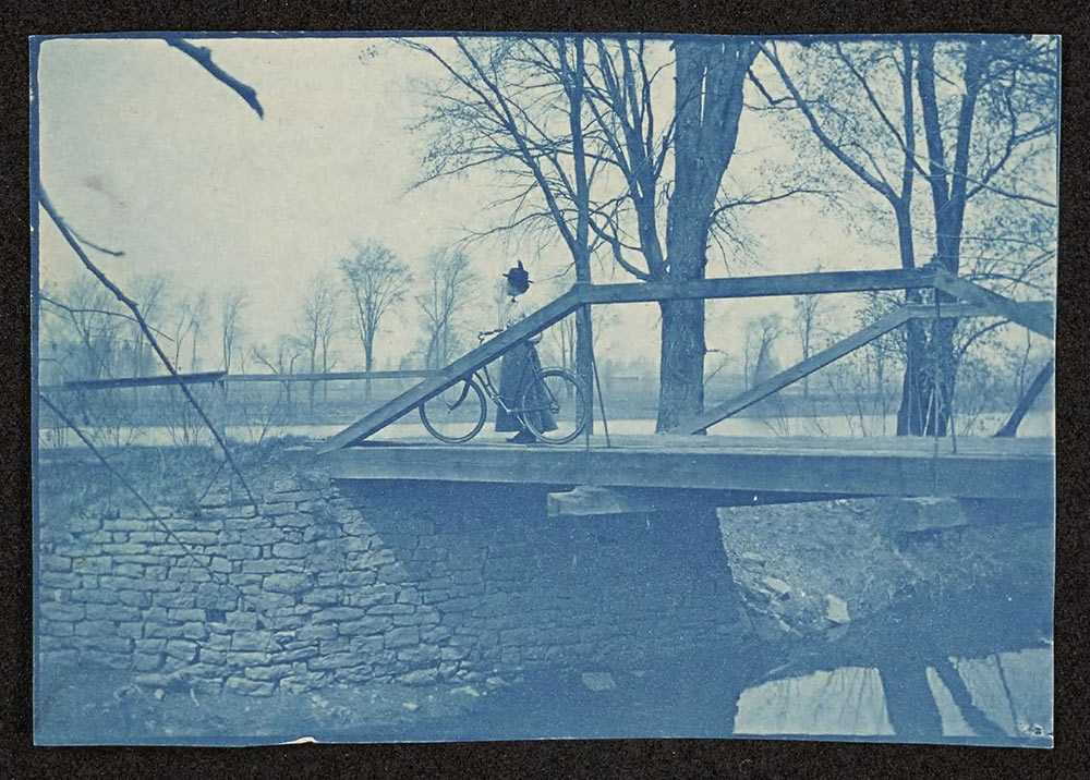 Woman with her bicycle on a bridge in the year 1899
