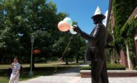 George Eastman statue wearing birthday hat and holding balloons