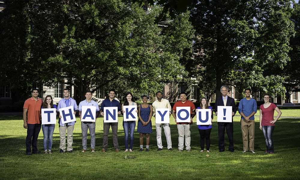 students and university president pose holding letters that spell out THANK YOU.