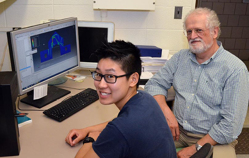 student with professor in front of computer