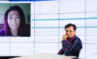 Ehsan Hoque in front of computer screen with inset of another person's face