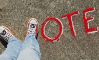 chalk on sidewalk spells out VOTE