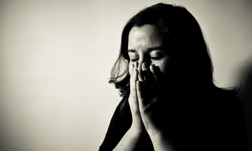 stressed woman holding her hands to her face