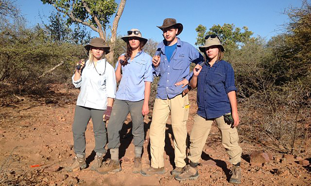 students pose with shovels at research site in Africa