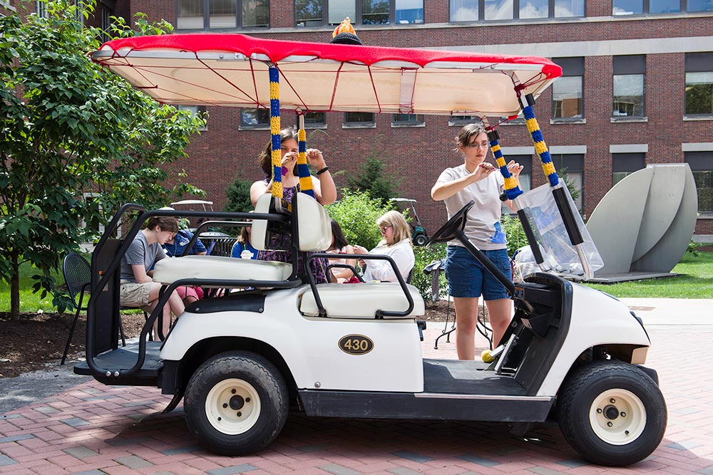 students knitting blue and yellow stripes onto a golf cart