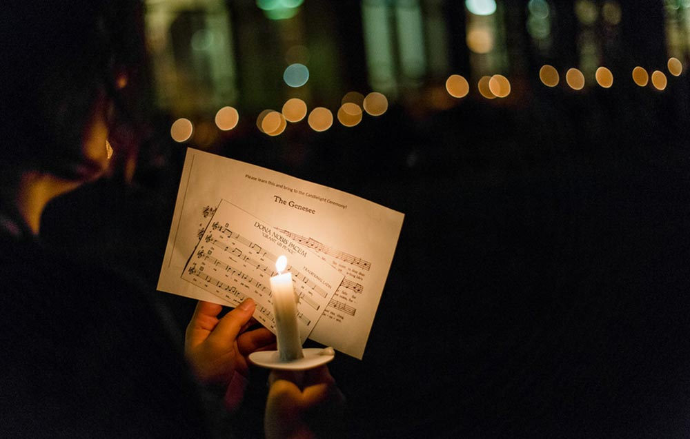student holding a candle in front of sheet music for THE GENESSEE