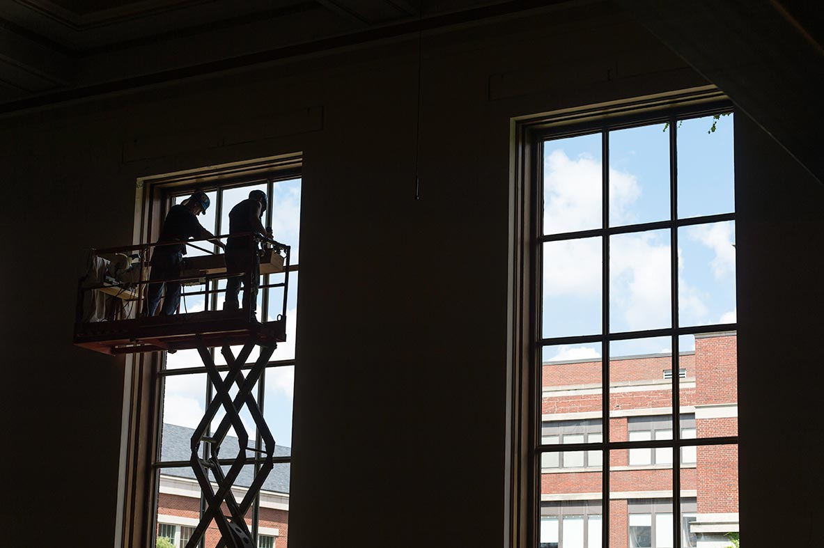 workers on a construction lift in front of large windows in Strong Auditorium