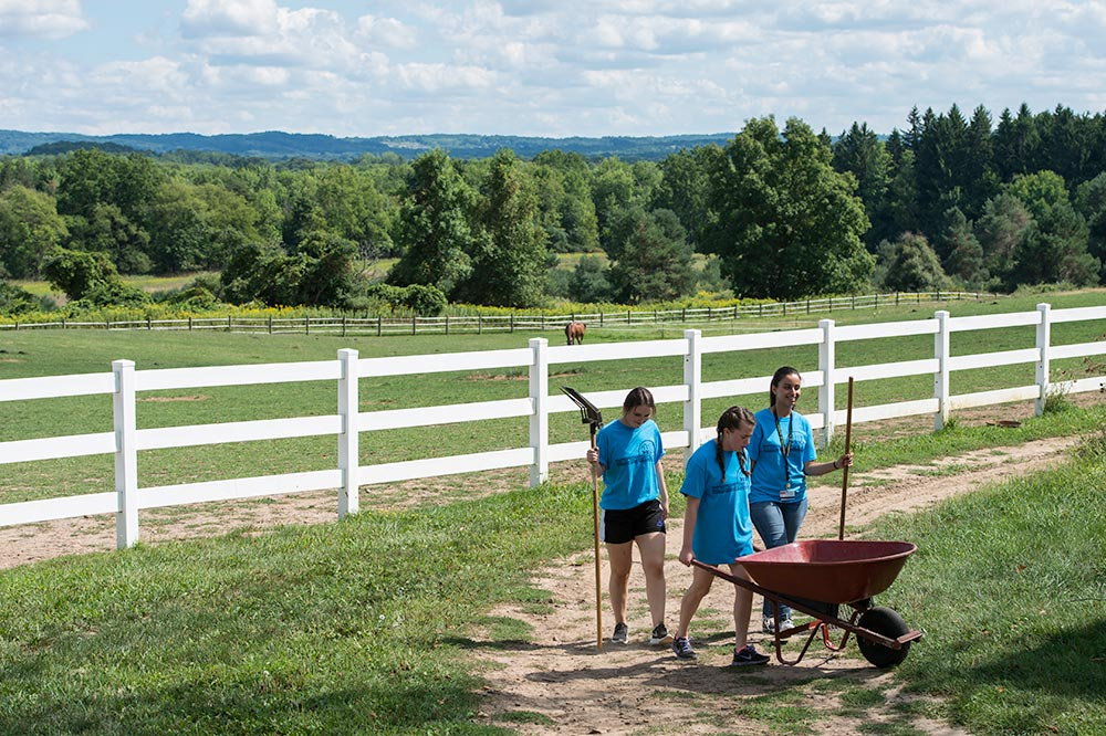 student pushing a wheel barrow, with horses in the backgroun