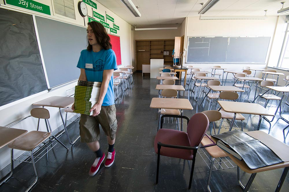 student in empty classroom carrying books