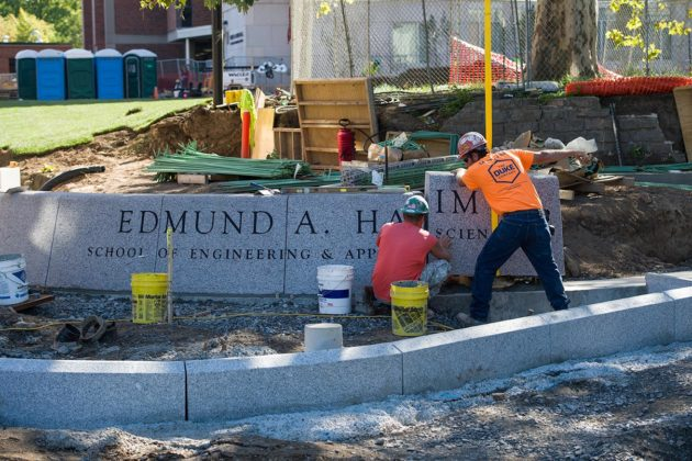 workers lower a piece of a granite sign into place; sign reads EDMUND A. HAJIM SCHOOL OF ENGINEERING AND APPLIED SCIENCES