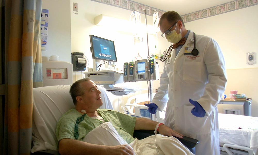 patient in hospital bed talks to doctor