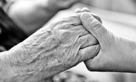 two hands, one elderly one younger