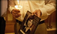 person holding photo and a candle at memorial service