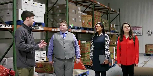 four students standing in warehouse