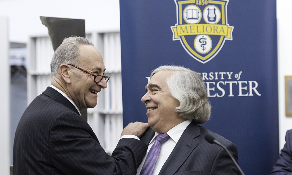 Chuck Schumer and Ernest Moniz in front of University of Rochester banner