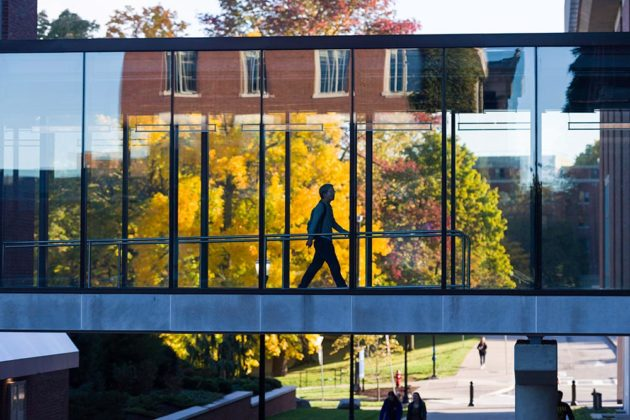 student walking across elevated bridge walkway with fall trees in background