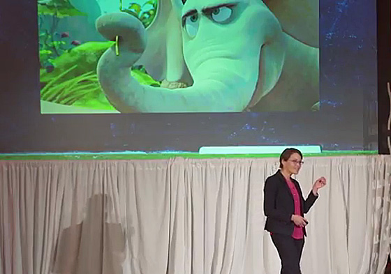 professor in front of a screen with an image of an animated elephant