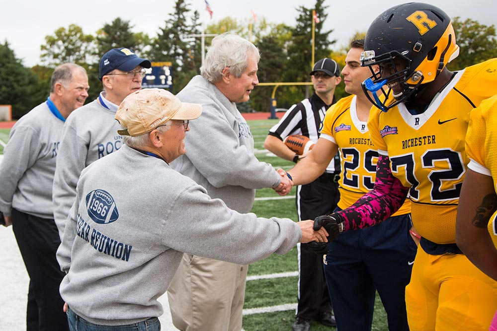 Current members of football team shaking hands with alumni from Class of 1966