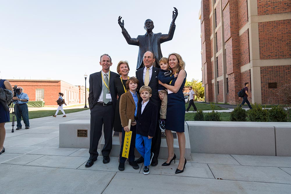 family poses in front of statue