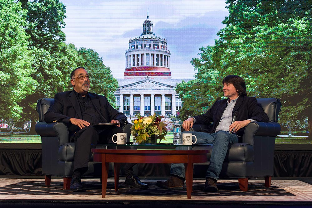 Paul Burgett and Ken Burns seated on stage