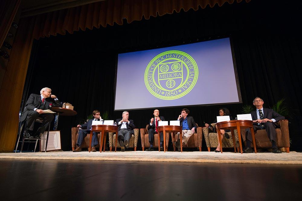 panel of speakers seated on stage
