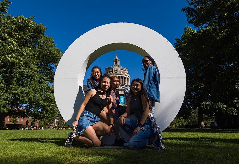 students pose inside giant letter O